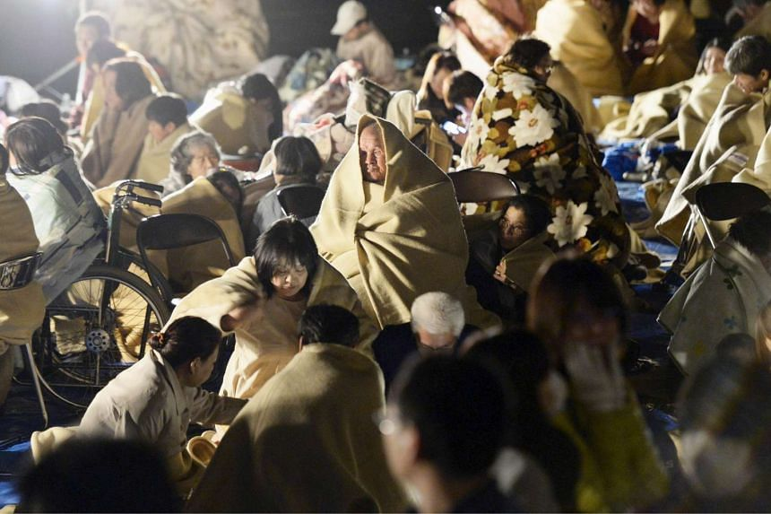Residents of Mashiki wrap themselves in blankets as they sit on the road in front of the town office building after an earthquake in Japan's Kumamoto prefecture.