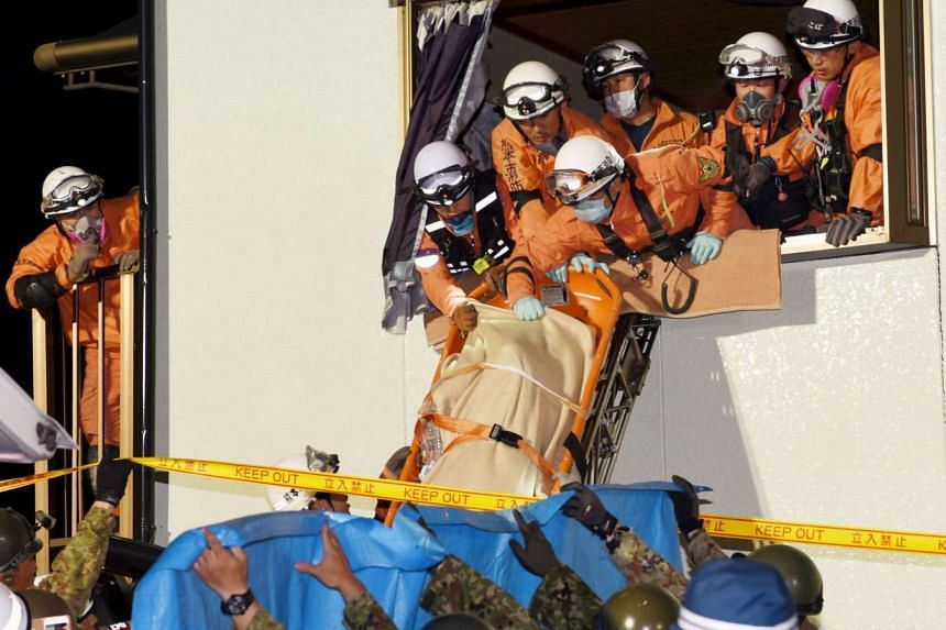 Rescue workers using a stretcher to carry a woman who was rescued from a collapsed house in Mashiki town, Kumamoto prefecture, southern Japan, in this photo taken by Kyodo on April 15, 2016.