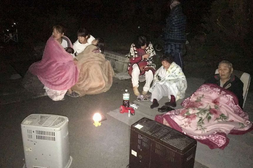 Local residents wrapping themselves in blankets as they sit on the road after they are evacuated from their home after an earthquake in Mashiki town, Kumamoto prefecture, southern Japan, in this photo taken by Kyodo on April 15, 2016.