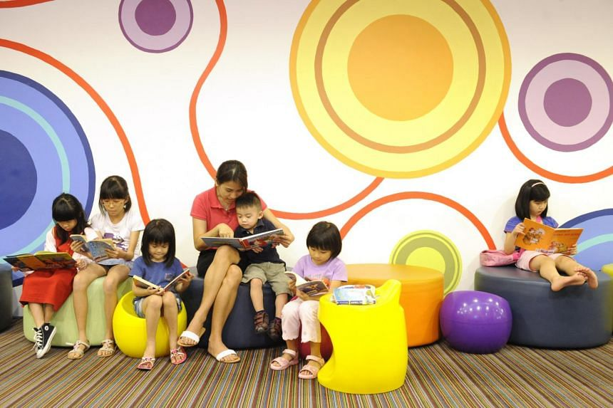 A woman and a group of children reading books at Bishan public library.