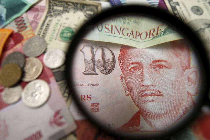 Singapore currency notes are seen through a magnifying glass among other currencies.