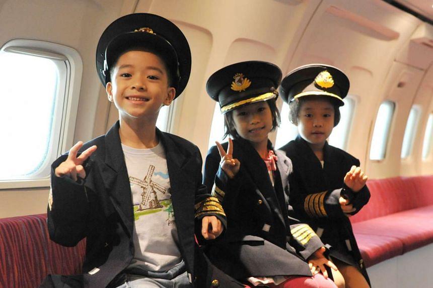 Seven-year-olds (from left) Goh Yu Di, Huang Jing Yi and Zhou Shu Mei role-playing as pilots at KidZania.
