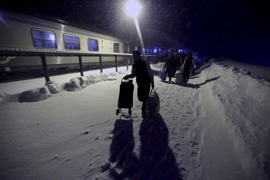Refugees disembarking a train in Riksgransen, Sweden, and making their way on Dec 15 to a camp at a hotel touted as the world's most northerly ski resort.