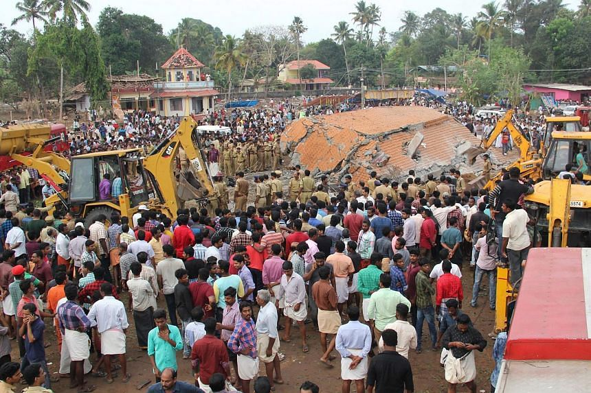 People gather at the spot where a fire triggered by fireworks resulted in an explosion and a roof collapse at a temple in Kollam, India, on April 10, 2016.