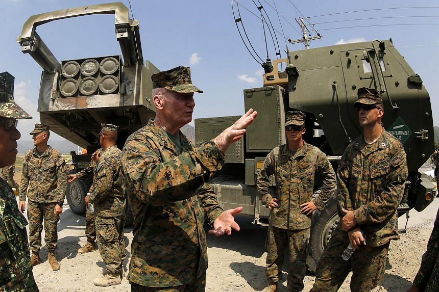 U.S. Marines Expeditionary commander in the Pacific, Lieutenant General John Toolan (centre) standing next to a High Mobility Artillery Rocket System (HIMARs) during joint military exercises at Crow Valley in the town of Capas, Tarlac province, Phili