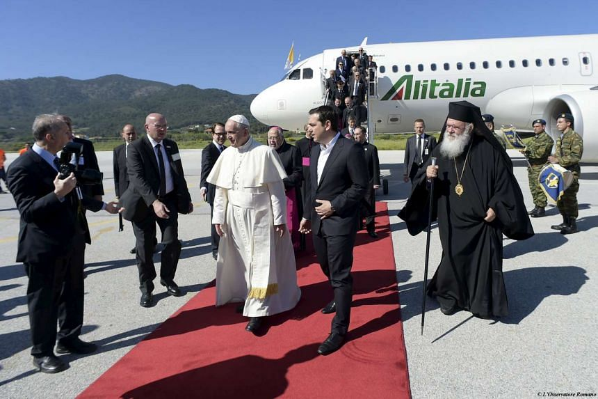 Pope Francis (centre) greeted by Greek Prime Minister Alexis Tsipras (second from right) and Archbishop Ieronimos (right) on the Greek island of Lesbos on April 16, 2016.