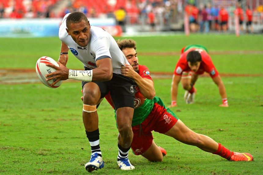 Fiji's Jasa Veremalua evading the challenge of Portugal's Pedro Silverio to score a try. Fiji won the match 38-0.