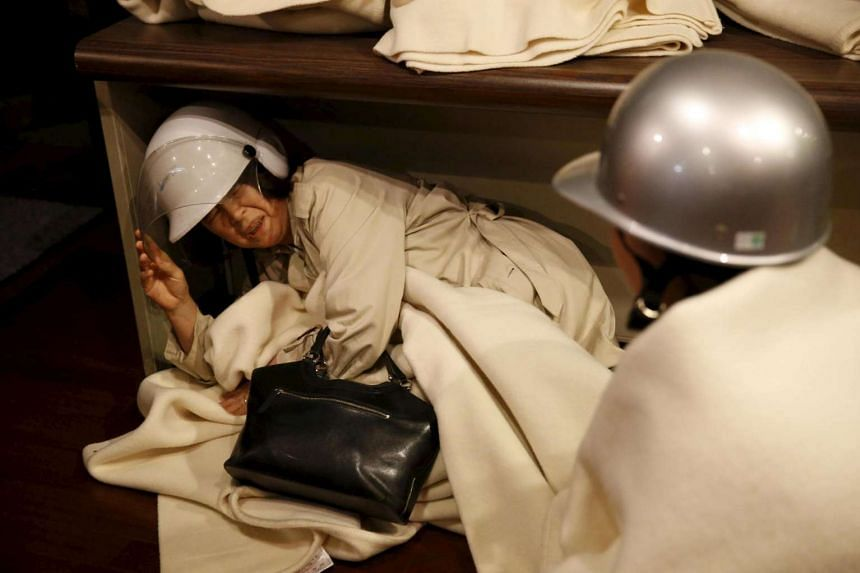 A woman takes shelter after another earthquake hit the area at a hotel in Kumamoto, southern Japan, in this photo taken by Kyodo on April 16, 2016.