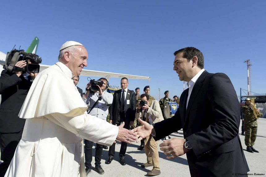Pope Francis is greeted by Greek Prime Minister Alexis Tsipras (right) on the Greek island of Lesbos on April 16, 2016.
