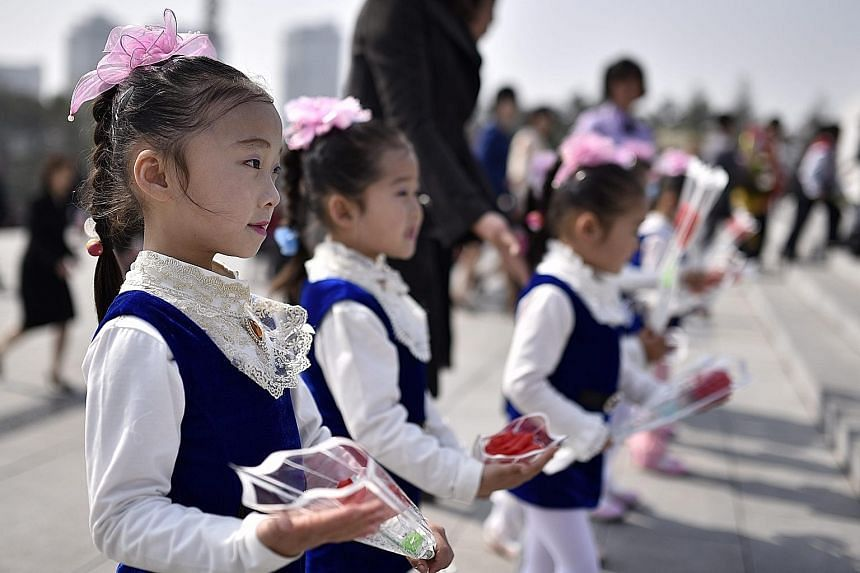North Korean school children (above left) paying respects to the country's late founding father Kim Il Sung whose birthday was yesterday. Statues of Kim Il Sung (with raised hand) and his son Kim Jong Il outside Mansu Hill in Pyongyang on the Day of