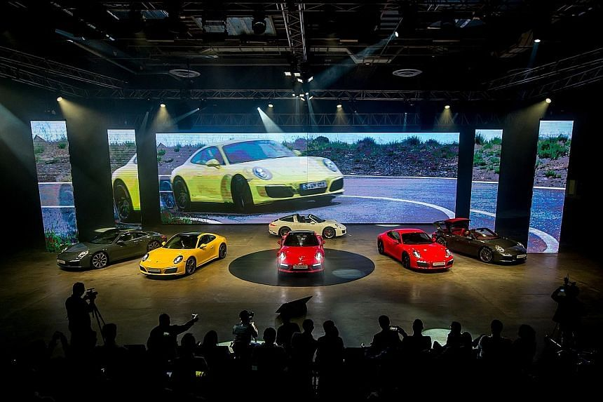 Singapore tycoon S.K. Quek with his Lightweight E-Type, unveiled by Jaguar agent Wearnes Automotive on Wednesday. Cars launched this week included Porsche 911s (above) and the GTA Spano supercar (left).