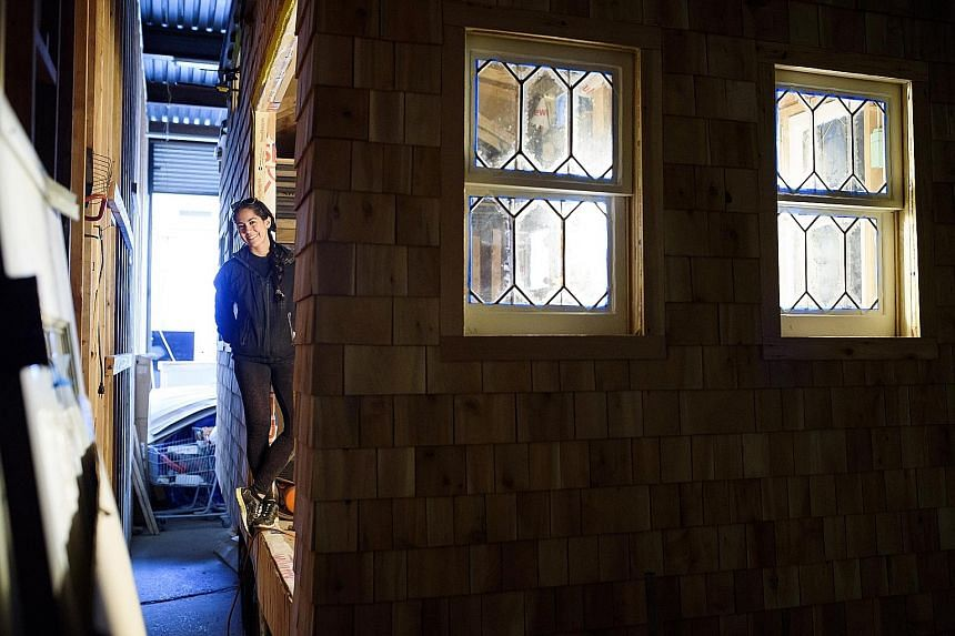Ms Miko Mercer (above) is building her 160 sq ft house (above right) in a warehouse in Brooklyn.
