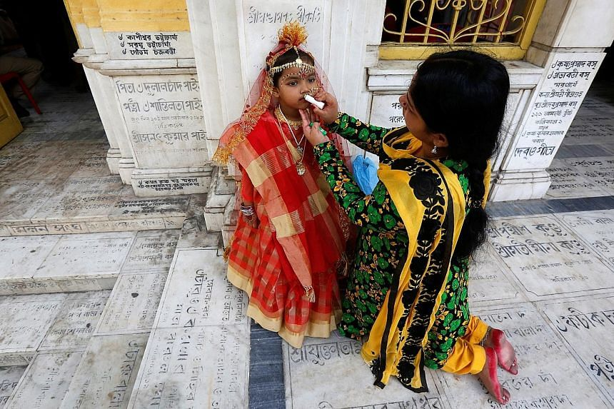 The mother of a young girl applying lip gloss on her daughter before the start of rituals to commemorate the Hindu festival called Navratri, at Adyapith temple on the outskirts of Kolkata, India, yesterday.