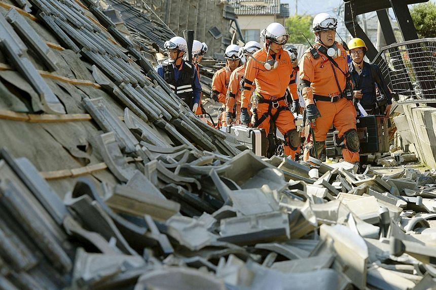 Firefighters looking for victims under collapsed houses in the aftermath of a magnitude-6.5 earthquake in Mashiki town, Kumamoto prefecture, in south-western Japan yesterday. The quake killed nine people, injured at least 1,000 and cut power and wate