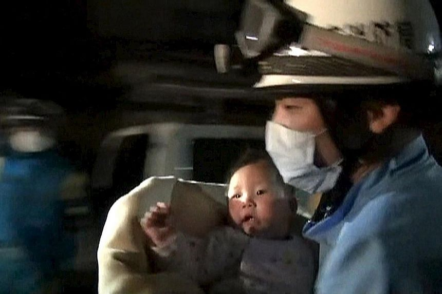 Eight-month-old baby Miku in the arms of a rescue worker after she was pulled out out unhurt from a collapsed house in Mashiki town, more than six hours after a magnitude-6.5 earthquake struck Kyushu on Thursday.