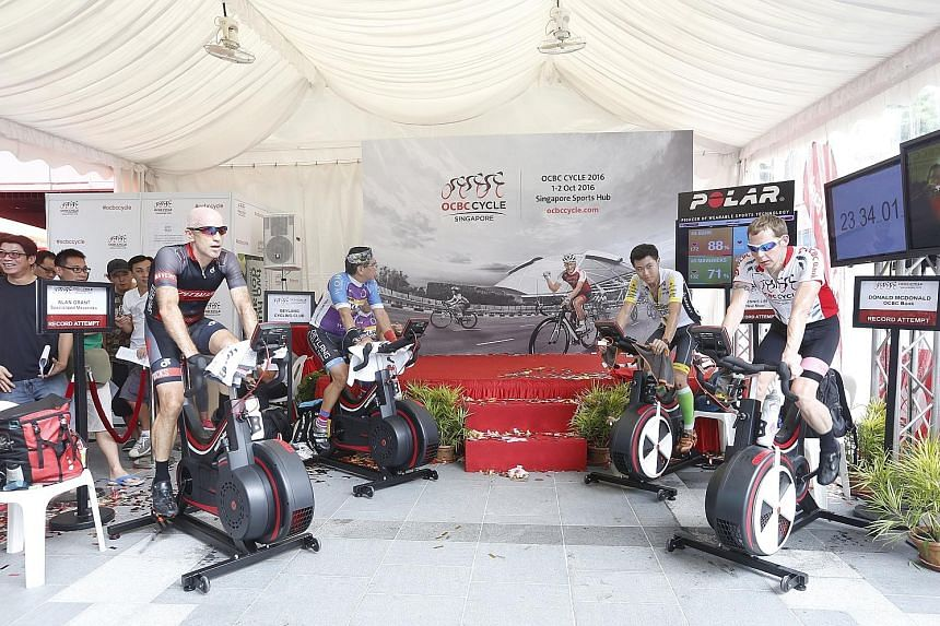 """Above: Four teams of riders pedalling for 24 hours on stationary bikes with the aim of breaking the record for """"Longest Distance Covered on a Stationary Bike in Six Hours"""". Left: ST sports editor Marc Lim (right) presenting OCBC CEO Samuel Tsien with"""