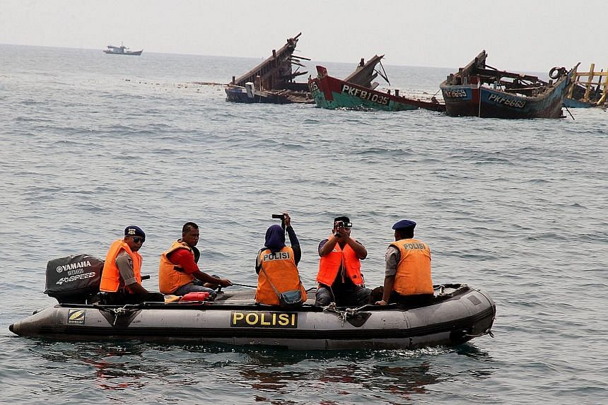 Police officers near the wreckage of illegal fishing boats blown up by Indonesian authorities in Kuala Langsa, Aceh province, earlier this month.