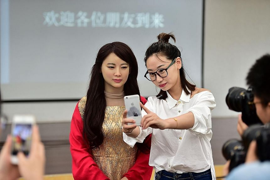"""""""Jiajia"""" an interactive robot (left), """"posing"""" for a wefie with a journalist during its debut yesterday in Hefei, capital of east China's Anhui Province. Developed by the University of Science and Technology of China, Jiajia is able to engage in simp"""