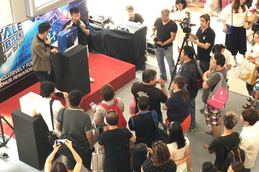 Shoppers bidding for a Sony Playstation 4 at Funan Digitalife Mall on Saturday (April 16) in the mall's Believe IT or Not sale activities. The sale lasts till Sunday.