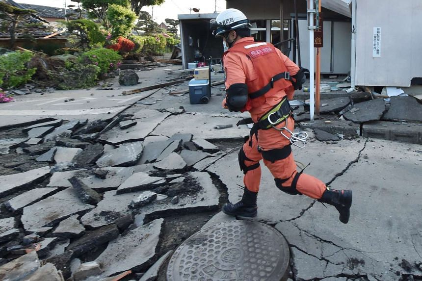 A member of a rescue team running on a street cracked by the earthquake in Mashiki, Kumamoto prefecture on April 16, 2016.