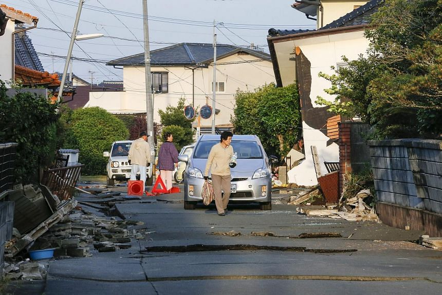 Residents walking through damaged houses in Mashiki, Kumamoto Prefecture on April 16, 2016, after a strong earthquake hit south-western Japan in the early morning.