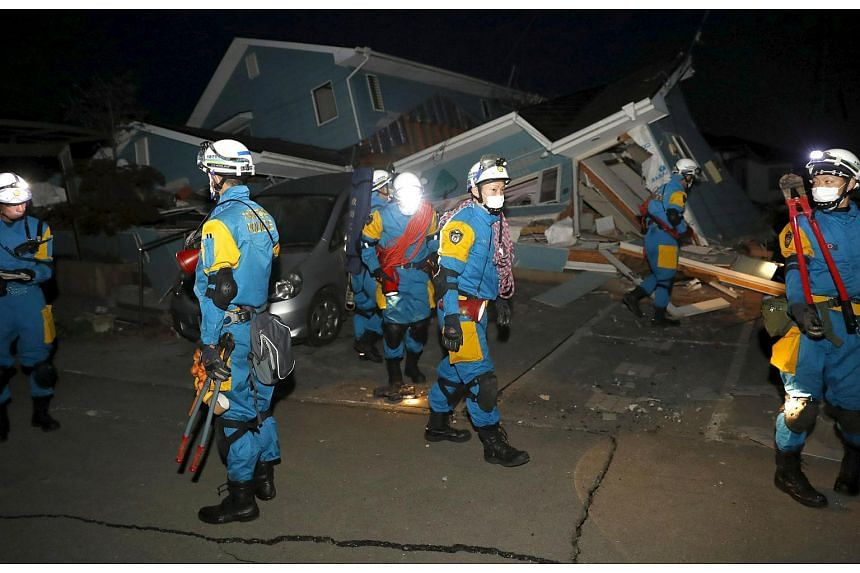 Police officers checking a collapsed house after an earthquake in Mashiki town, Kumamoto prefecture, southern Japan, in this photo taken by Kyodo on April 16, 2016.