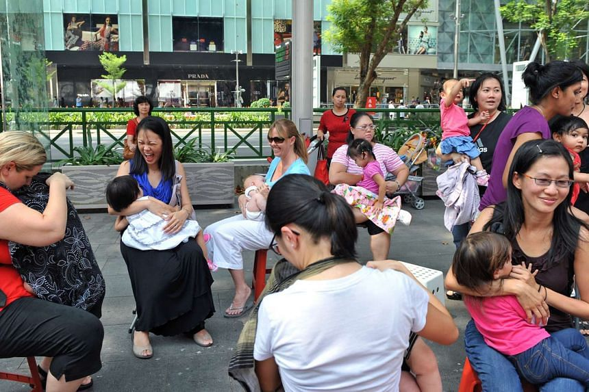 """Housewife Chin Wee Kean (front row, right), with her daughter Tabitha Ingram, was among more than 15 mothers who gathered at Orchard Road for """"Latch on for Love"""" to breastfeed their babies and toddlers in a flashmob exercise to promote breastfeed"""