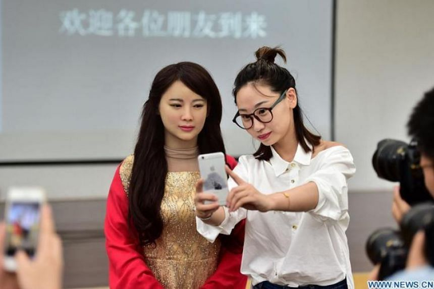 "Interactive robot ""Jiajia"" (left) at an unveiling with Chinese media."
