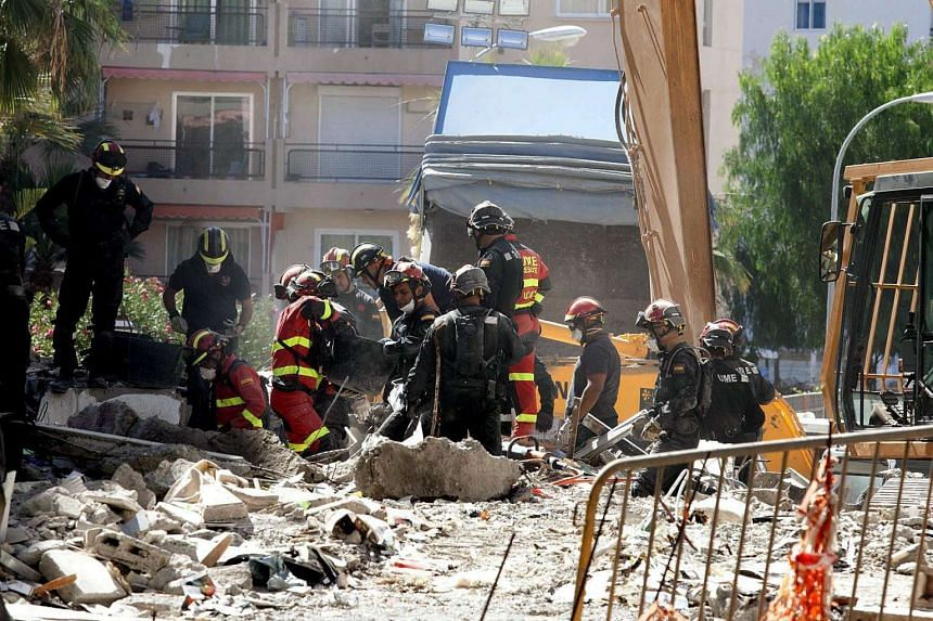 Several firefighters work in the search of victims among debris of a collapsed building in Los Cristianos, Arona, southern Tenerife Island, Canary Islands on April 16, 2016.