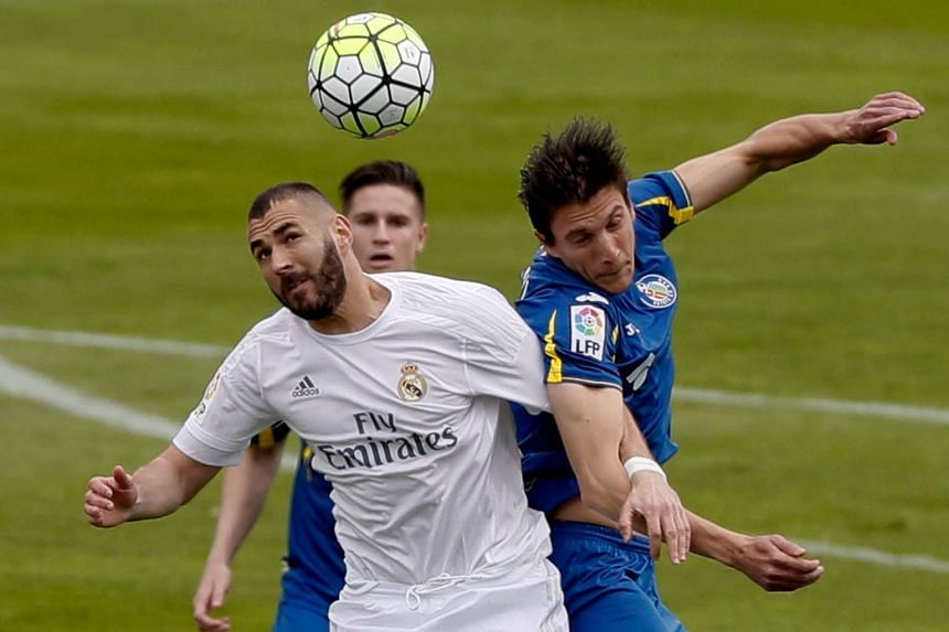 Real Madrid's French striker Karim Benzema (left) fights for the ball with Argentinian defender Santiago Vergini (right) of Getafe FC during their Primera Division soccer match played at Coliseum Alfonso Perez stadium in Getafe, Madrid, Spain on Apri