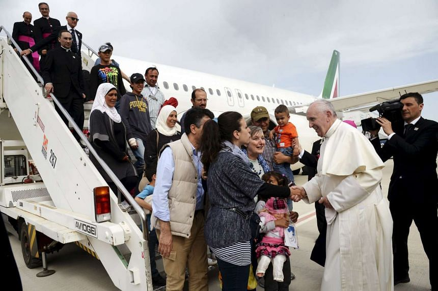 Pope Francis welcomes a group of Syrian refugees after landing at Ciampino airport in Rome.