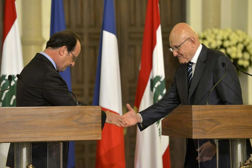 French President Francois Hollande (left) shakes hands with Lebanese Prime Minister Tammam Salam during a joint press conference after their meeting at the government palace in downtown Beirut, Lebanon, on April 16, 2016.