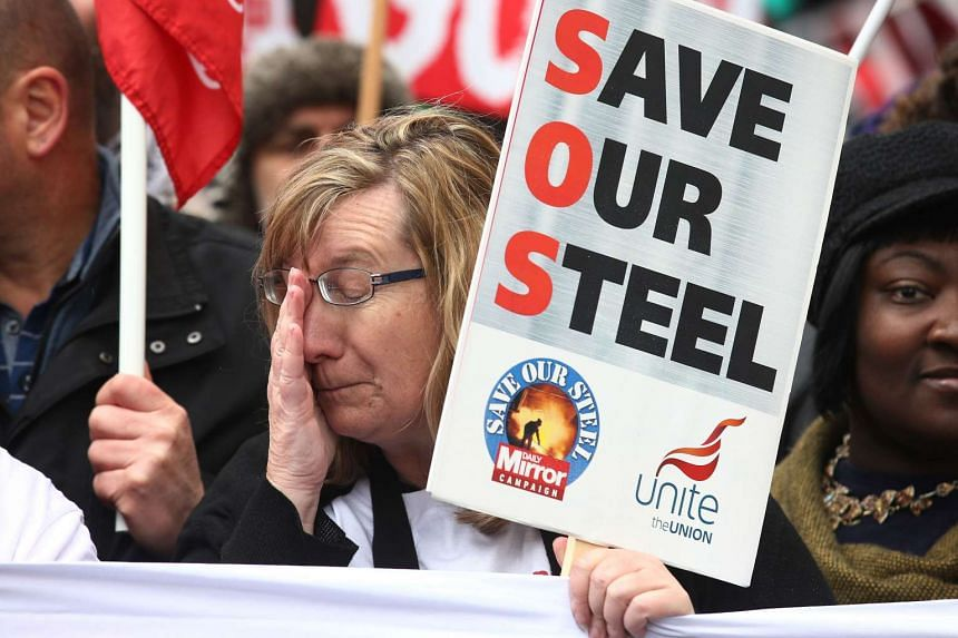 """Protesters hold placards that read """"Save Our Steel"""" during a demonstration organised by the People's Assembly Against Austerity in central London on April 16, 2016."""