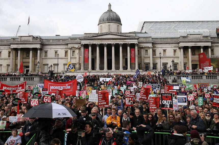 Protesters with placards and banners demonstrating on a variety of domestic issues, including a call for British Prime Minister David Cameron to stand down, listen to speeches in Trafalgar Square after marching in central London on April 16, 2016.