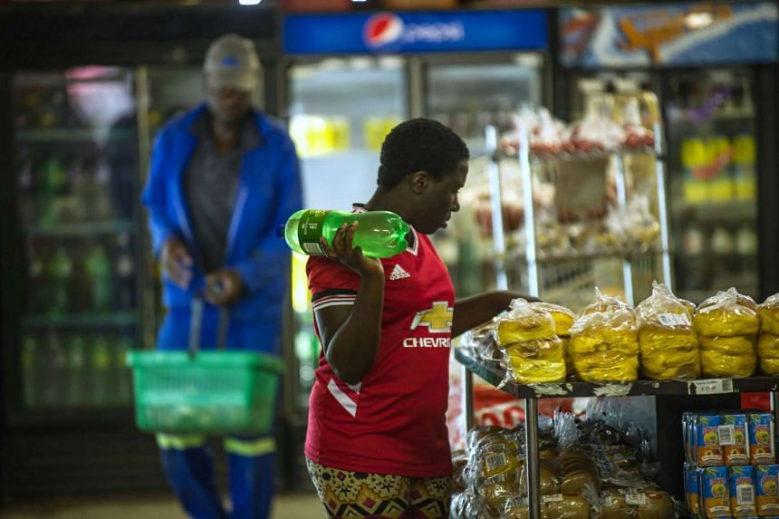 A woman holding a bottle of soft drink as she shops around at a local supermarket in Zandspruit, South Africa on March 15, 2016.