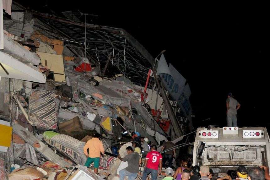 People standing next to the debris of a building after an earthquake struck off the Pacific coast, in Manta, Ecuador, on April 16, 2016.
