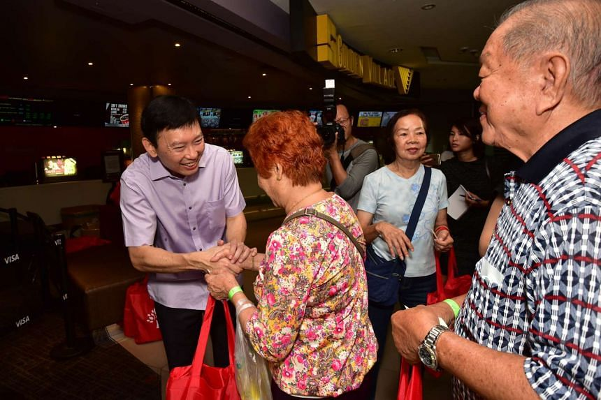 Mr Chee Hong Tat handing out gift bags to seniors who attended the movie screening.