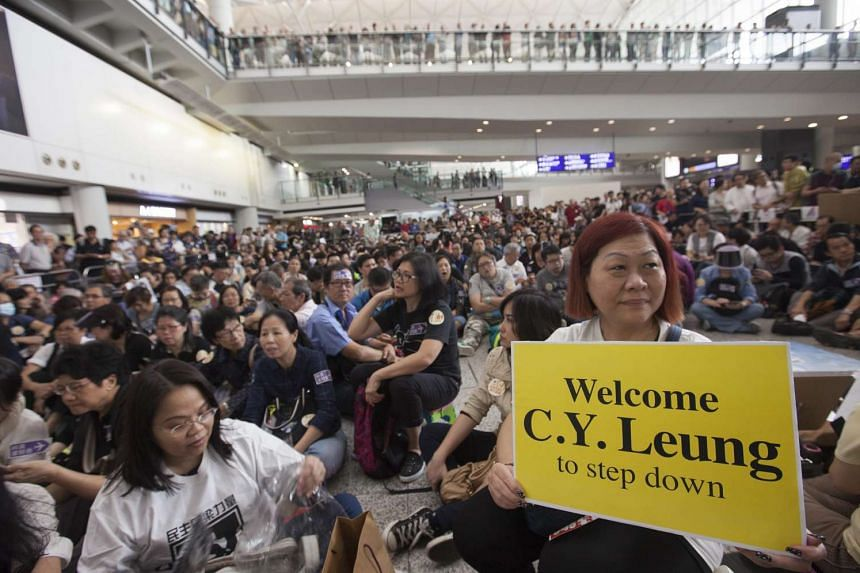 Demonstrators protesting against privileges allegedly extended to Hong Kong Chief Executive Leung Chun Ying's daughter, at Hong Kong's International Airport on April 17, 2016.