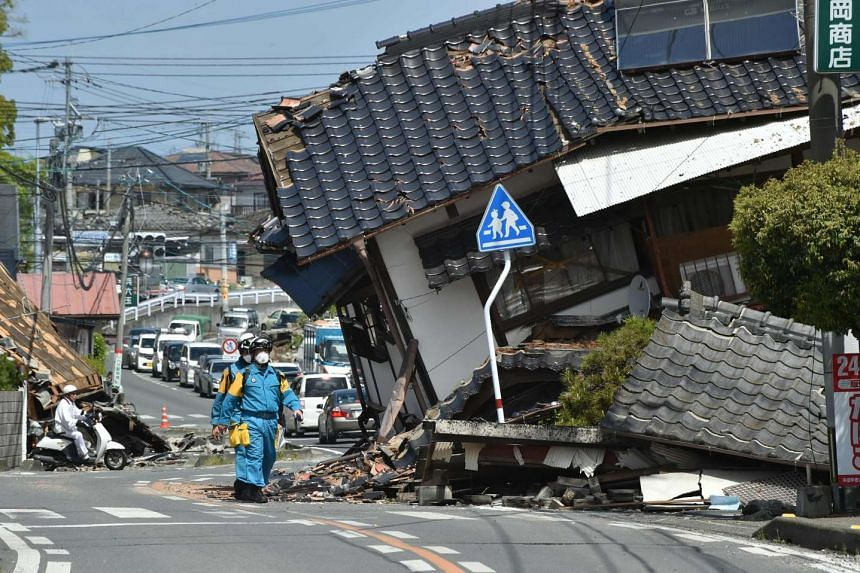 Policemen searching for missing people following the earthquakes in Mashiki, Kumamoto prefecture, on April 17, 2016.