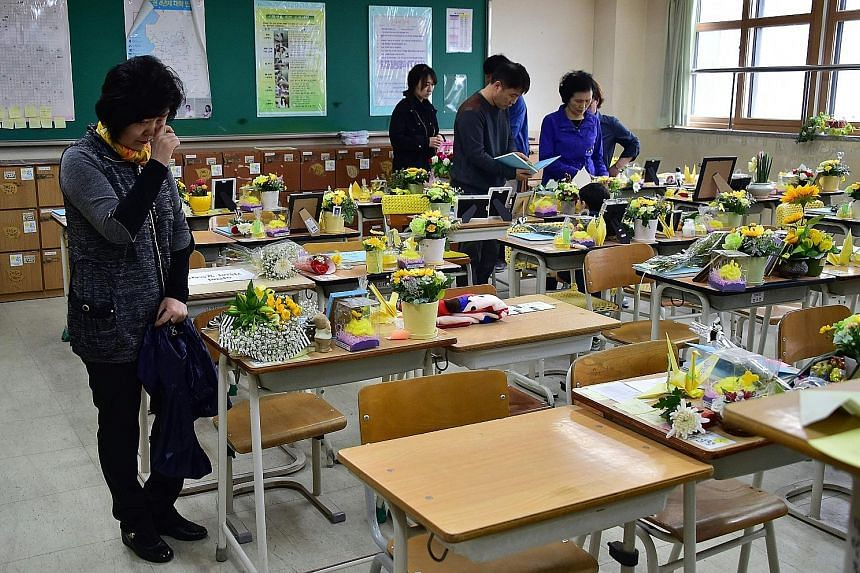 Visitors looking at tributes to the victims of the Sewol ferry disaster in a classroom at Danwon High School in Ansan, the victims' home city, yesterday. The tragedy claimed 304 lives.