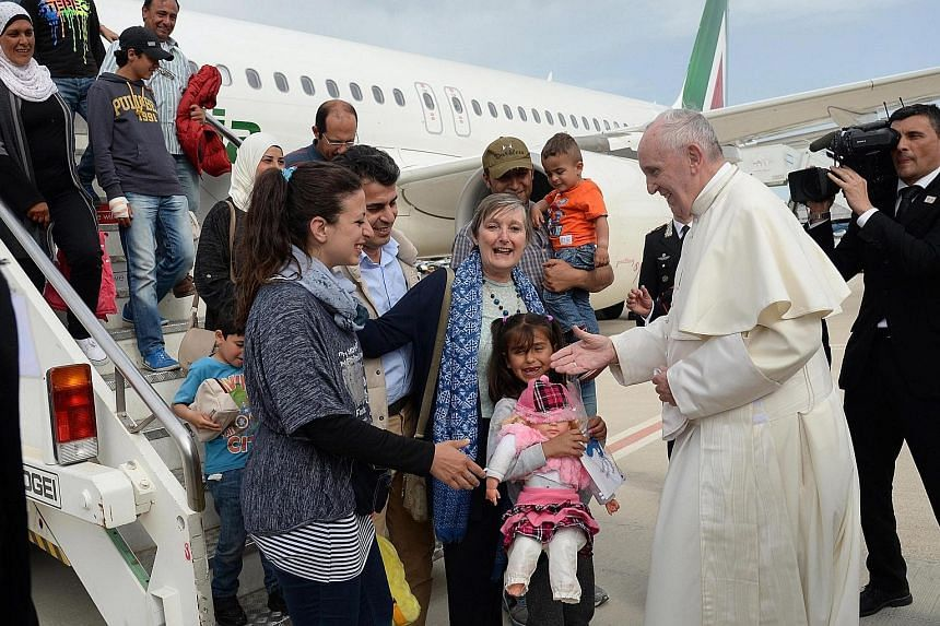 Pope Francis welcoming a group of Syrian refugees who flew in with him at Ciampino airport in Rome yesterday.