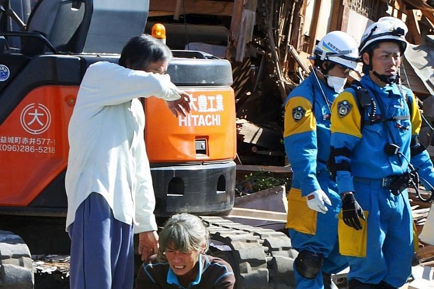 A couple crying after getting confirmation that their daughter was found dead at their house, which collapsed after an earthquake hit the town of Mashiki, in Kumamoto prefecture, yesterday. A landslide caused by an earthquake in Minamiaso village, Ku