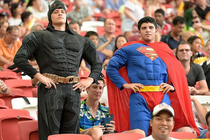 New Zealand's Sonny Bill Williams trying to break away from Canada's Pat Kay. New Zealand beat Canada 24-17 on Day 1 of the HSBC Sevens series in Singapore yesterday. This pair dressed as Batman and Superman were among the 23,000 enthusiastic rugby f