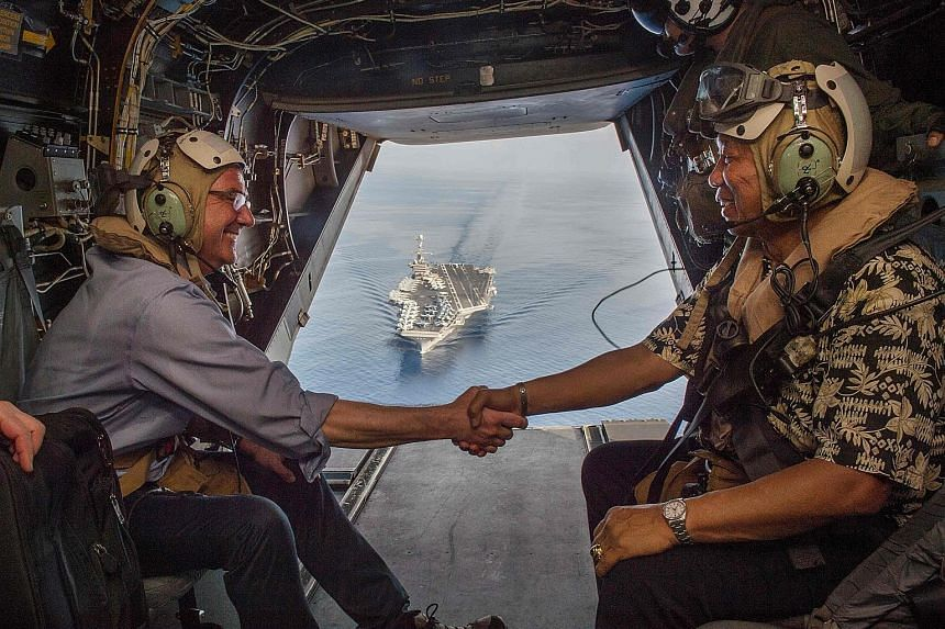 Mr Carter (left) and Philippine Secretary of National Defence Voltaire Gazmin in a Marine Corps V-22 Osprey as they depart the USS John C. Stennis last Friday.