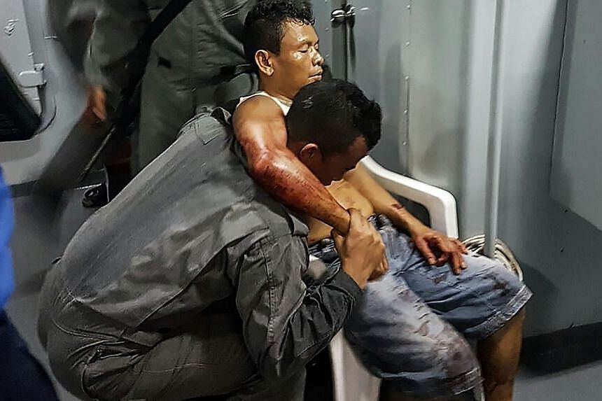 A member of the Malaysian Maritime Enforcement Force helping an Indonesian sailor who was shot while trying to resist capture by pirates, after the tugboat he was in was attacked in the South China Sea.