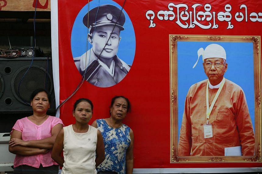 Relatives of detained activists stand near a poster with the images of Myanmar president Htin Kyaw.