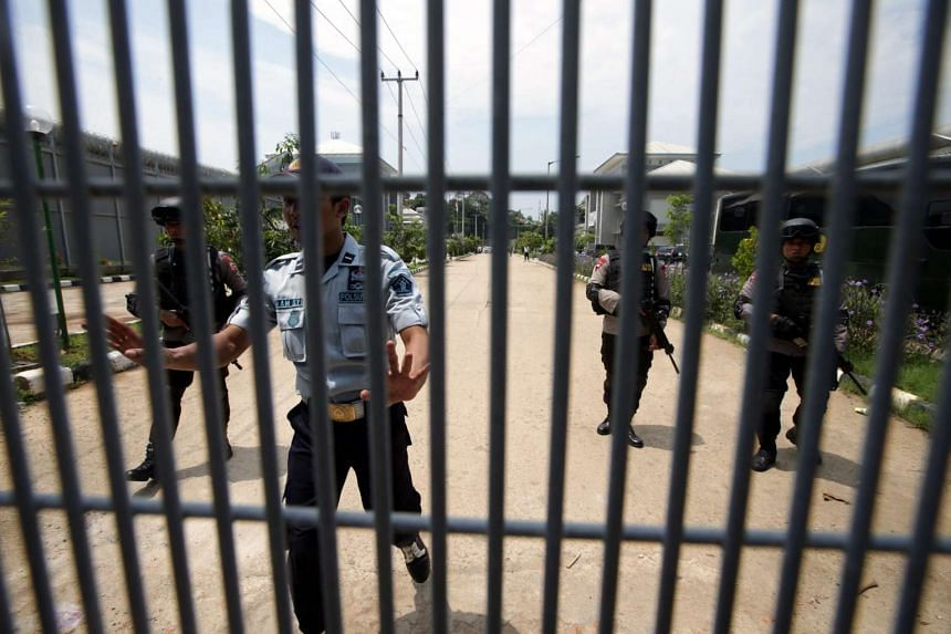 Indonesian police officers stand guard in front of the Gunung Sindur Prison after Indonesian Muslim cleric Abu Bakar Bashir was transferred to Gunung Sindur in Bogor, on April 16, 2016.