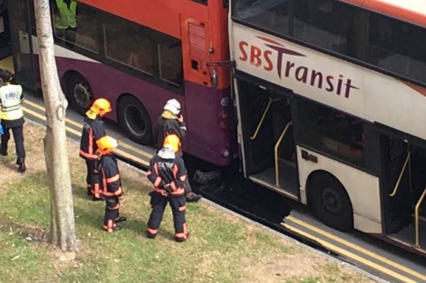 SCDF personnel assessing the damage to both buses.