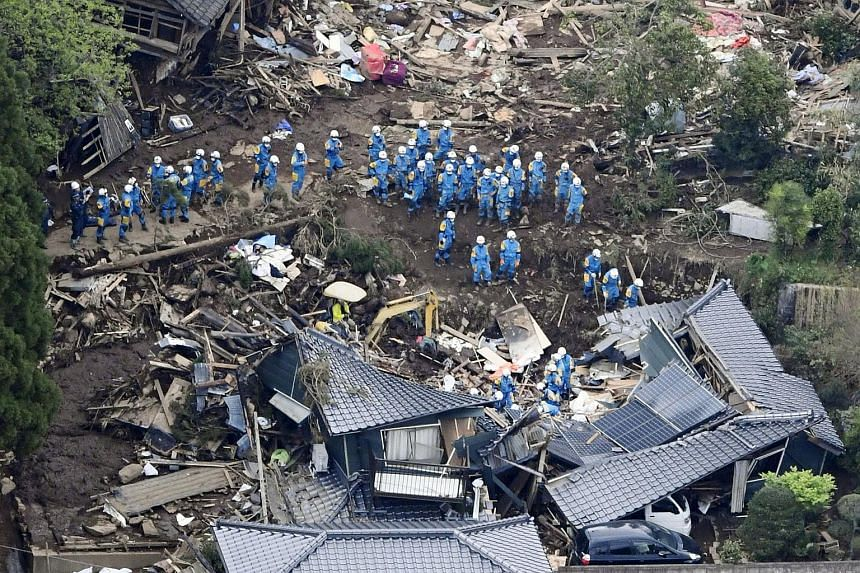 Rescue workers conduct a search and rescue operation to a collapsed house at a landslide site caused by earthquakes in Minamiaso town, Kumamoto, on April 16, 2016.