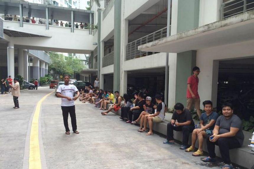 Residents sit on the ground floor of the apartment while police investigate the unit in Damansara Perdana.